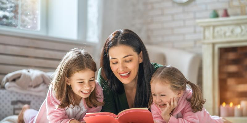 mother and daughters laying on floor on rug reading a book