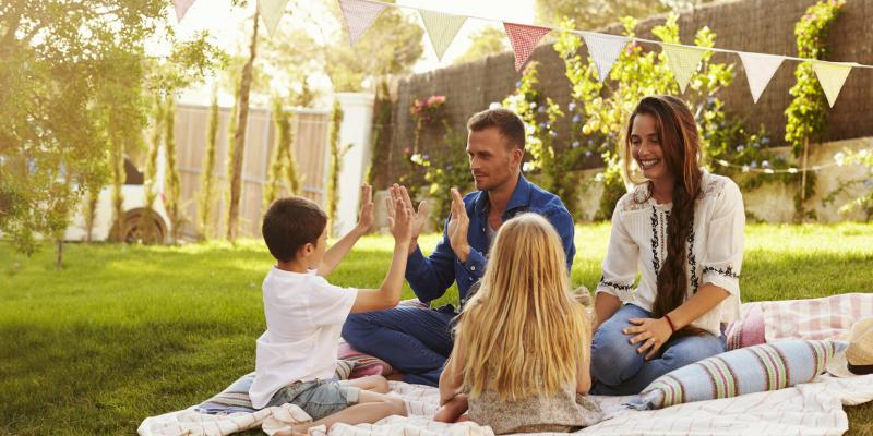 family on picnic blanket in yard