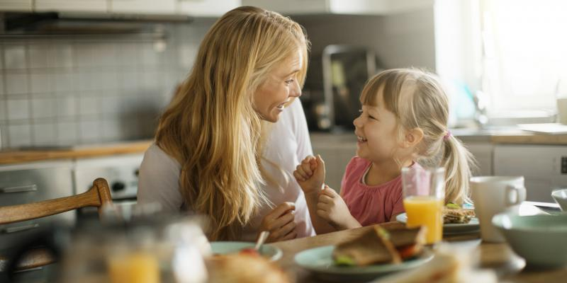 mom and daughter laughing and smiling in the kitchen