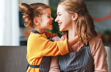mom and daughter smiling in kitchen